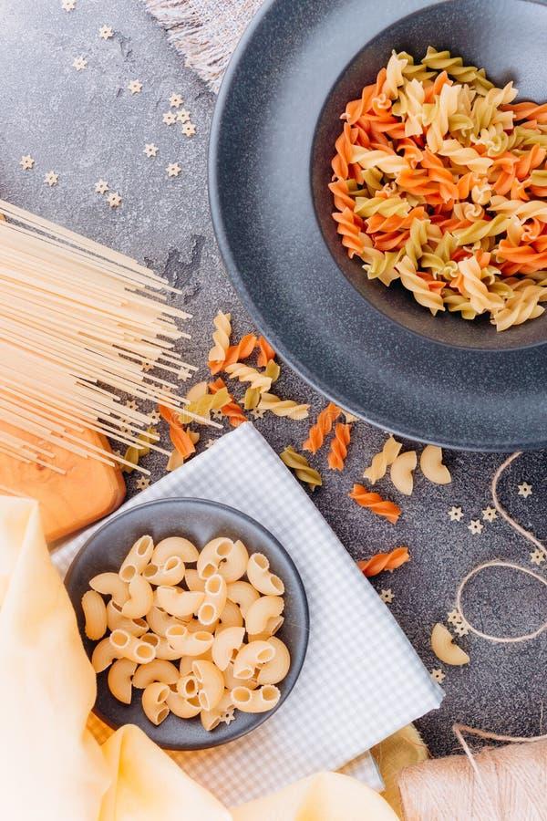 Olika typer av pasta p? en b?sta sikt f?r svart platta royaltyfri foto