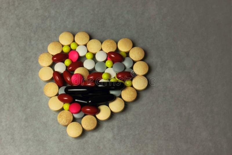 Olika typer av piller vikta i formen av en hjärta arkivfoton