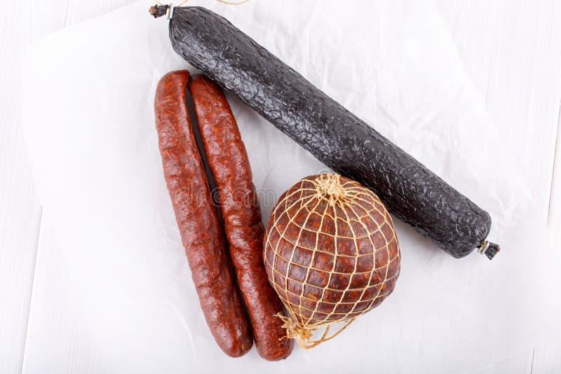 Olika typer av rökte salamikorvar på vit royaltyfri foto