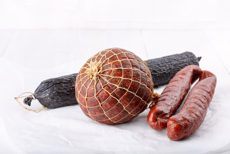 Olika typer av rökte salamikorvar på vit arkivbild