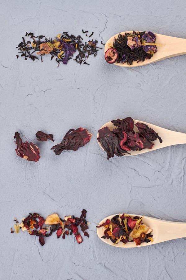 Olika typer av teblad i träskedar arkivfoto