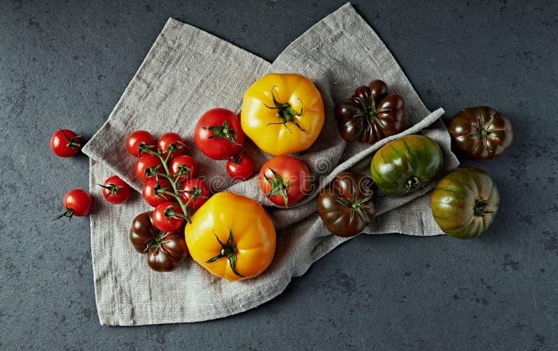 Olika typer av tomater på ett linnetyg Lekmanna- l?genhet royaltyfri fotografi