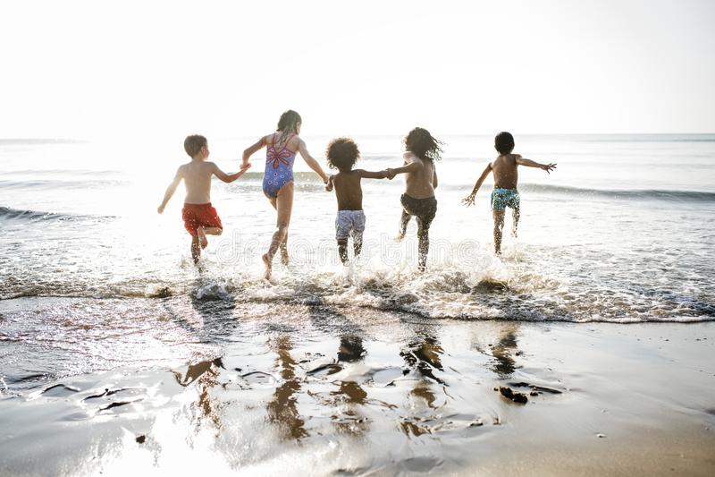 Olika ungar som kör på stranden royaltyfria foton
