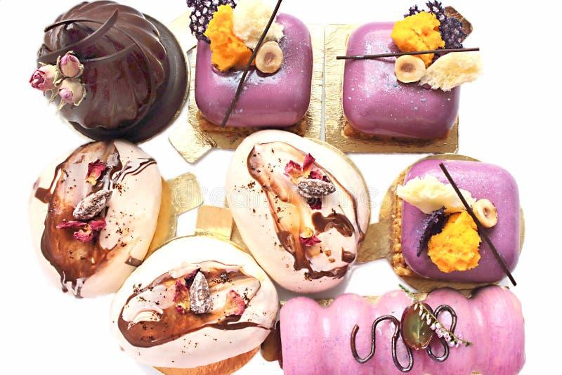 Olika utsmyckade efterrätter, purpurfärgad frukt-, choklad- och kaffeanstrykninguppsättning royaltyfria foton