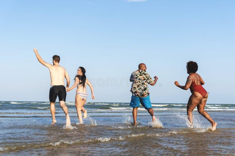 Olika vänner som har gyckel på stranden arkivbilder