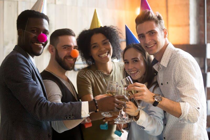 Olika vänner som klirrar champagneexponeringsglas som ser kameran cel royaltyfri bild