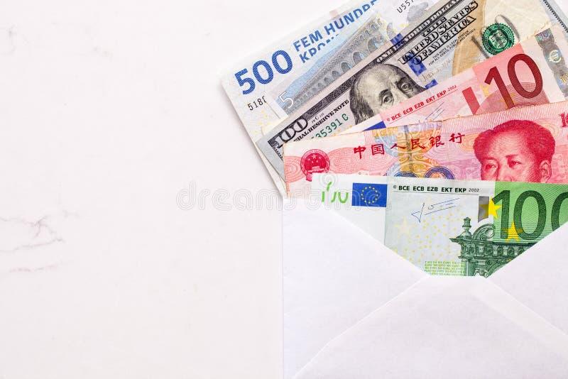 Olika världsvalutor, dansk kronner, euro och dollar räkningar i ett vitt kuvert på vitmarmorbakgrund arkivfoto