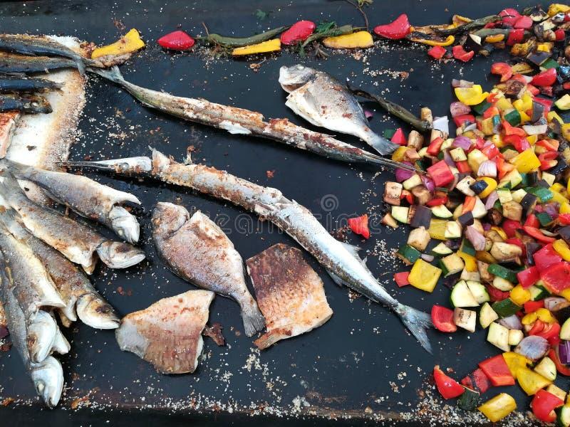 Olika variationer av fisken på gallret med grönsaker fotografering för bildbyråer