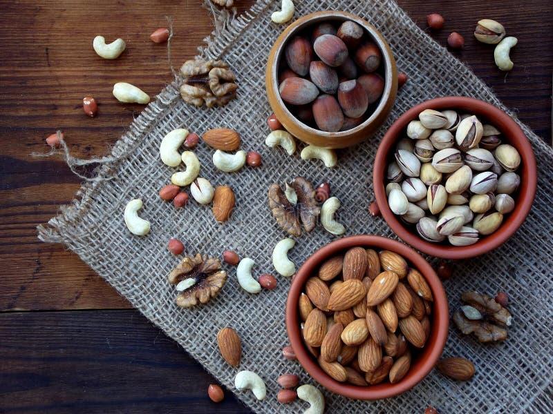 olika variationer av muttrar på en träbakgrund - mandlar, kasjuer, valnötter, hasselnötter, pistascher arkivfoto