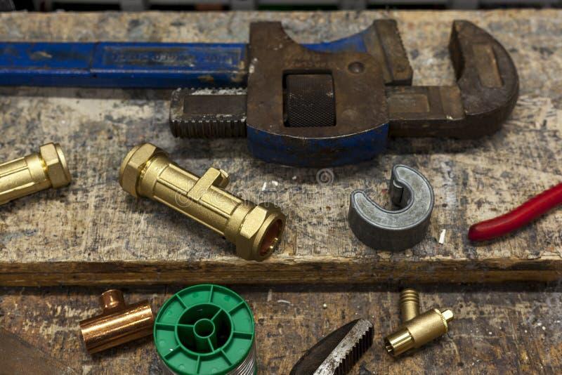 Olika ventiler och skiftnycklar på en rörmokarearbetsbänk royaltyfri bild