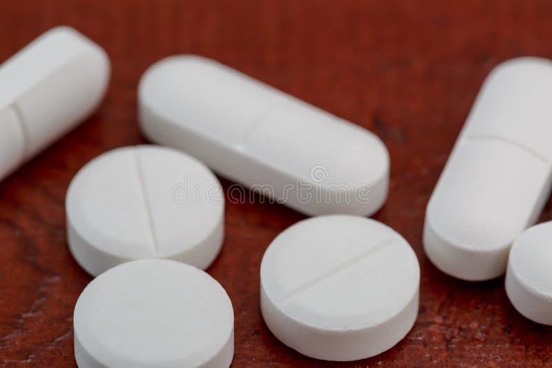 Olika vita preventivpillerar på trätabellen arkivbild