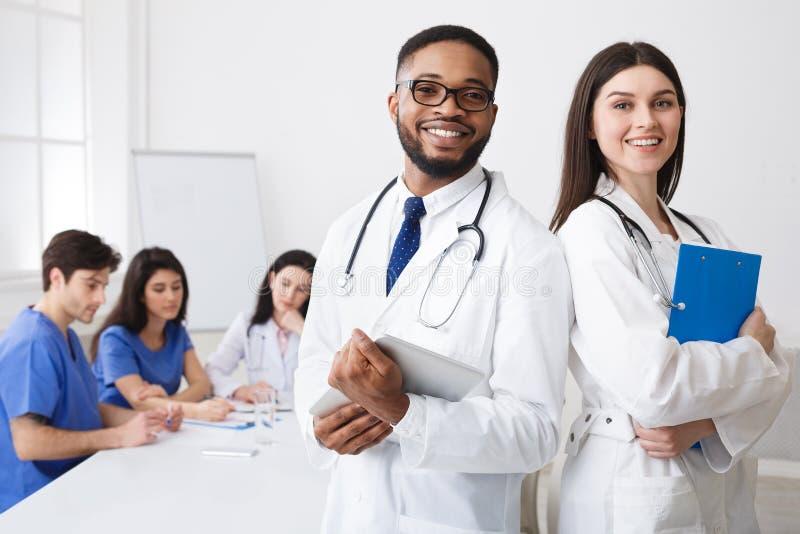 Olika yrkesmässiga doktorer i vita lag som poserar till kameran på arkivfoto