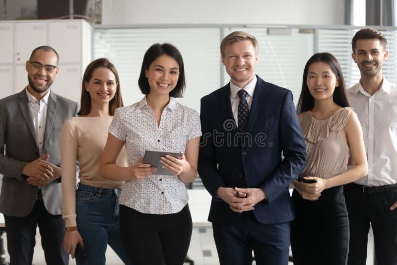 Olika yrkesmässiga företagsledare som i regeringsställning poserar med mångkulturella arbetare royaltyfri fotografi