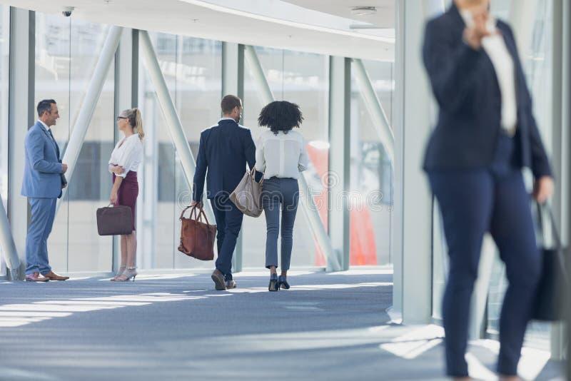 Olikt affärsfolk som går i korridor i modernt kontor fotografering för bildbyråer