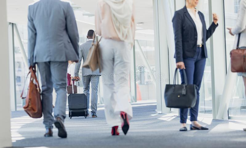 Olikt affärsfolk som går i korridor i modernt kontor arkivfoto