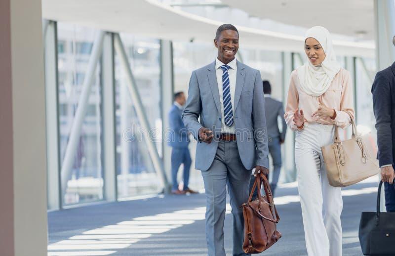 Olikt affärsfolk som går i korridor i modernt kontor arkivbild