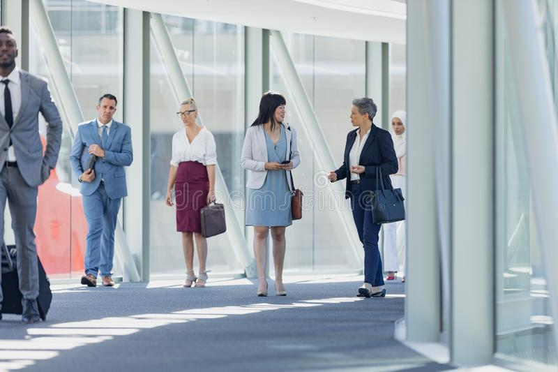 Olikt affärsfolk som går i korridor i modernt kontor royaltyfria bilder