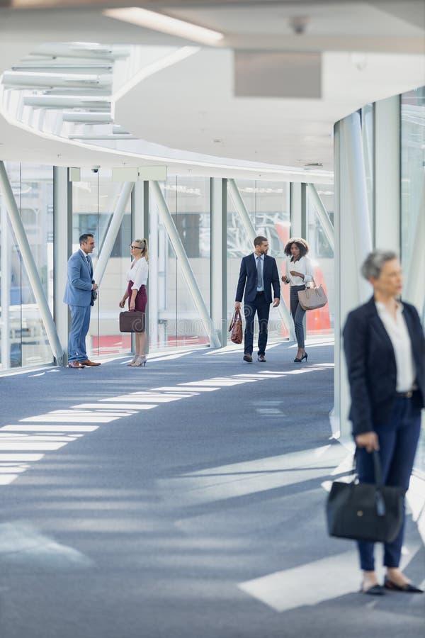 Olikt affärsfolk som går i korridor i modernt kontor arkivbilder