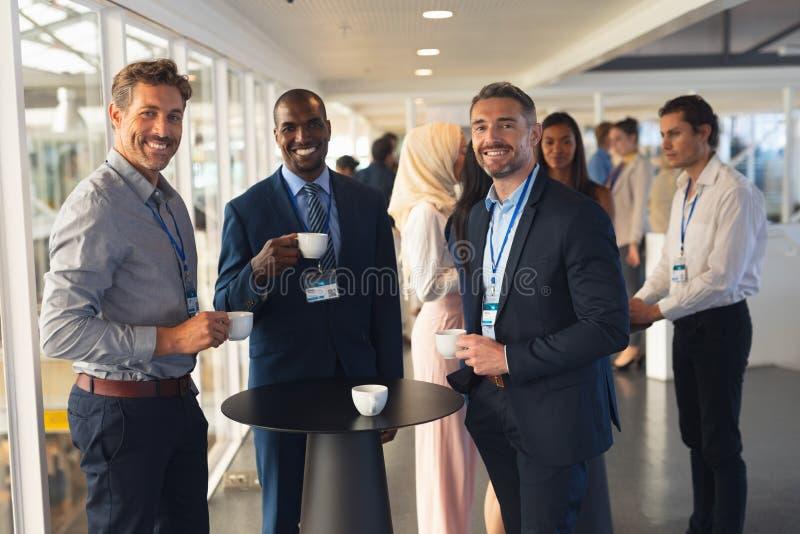 Olikt affärsfolk som har kaffe i regeringsställning royaltyfri foto