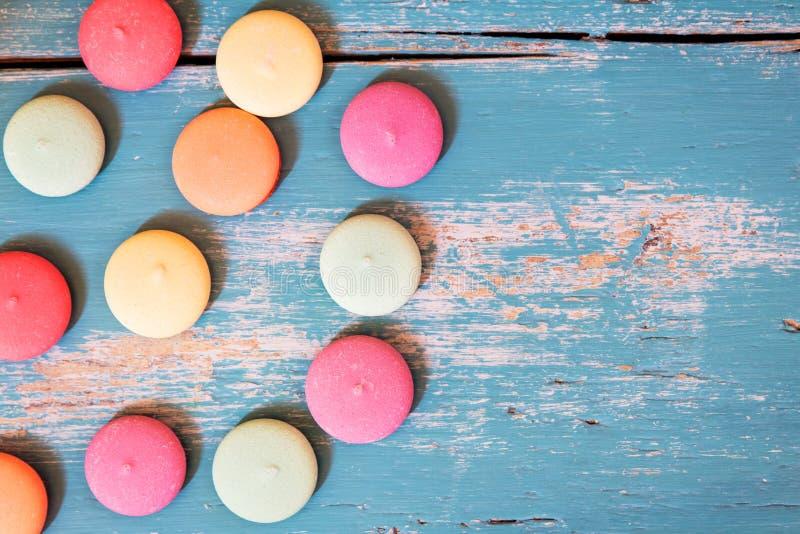Olikt av färgrika kex eller macarons på blå träbackgrou arkivfoto