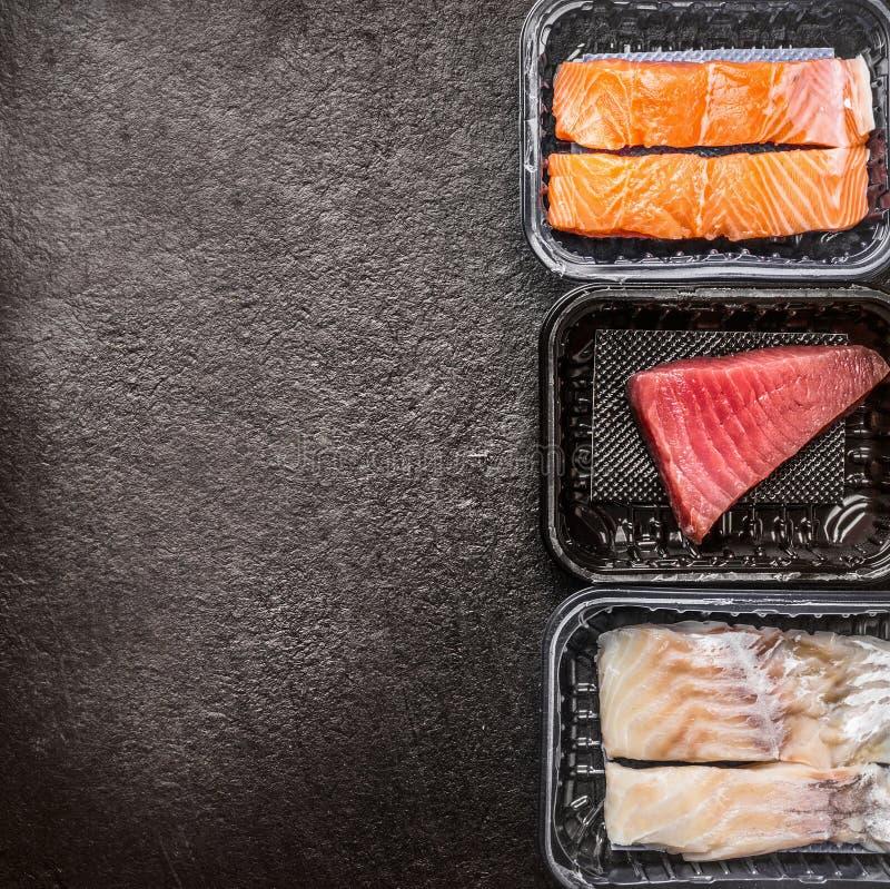 Olikt av filéer för rå fisk: lax, tonfisk och codfish i plast- askar på mörk lantlig bakgrund, bästa sikt, gräns, ställe för tex royaltyfri bild