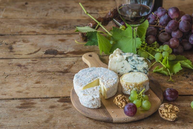 Olikt av franska ostar, muttrar, druvor och exponeringsglas av rött vin arkivfoto
