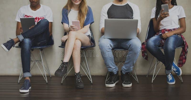 Olikt begrepp för stol för gruppungdomarDigital apparat royaltyfria foton
