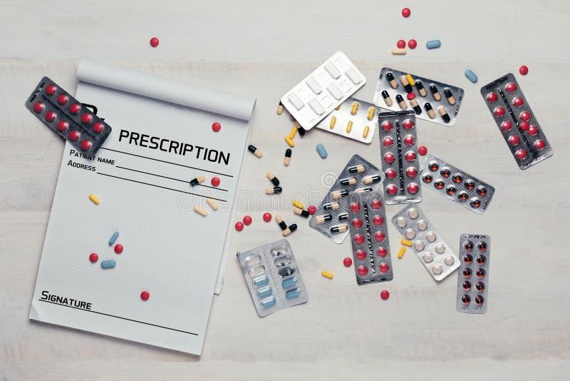 Olikt färgrikt preventivpillerar, minnestavlor, kapslar och recept på den vita trätabellen, bästa sikt royaltyfri bild