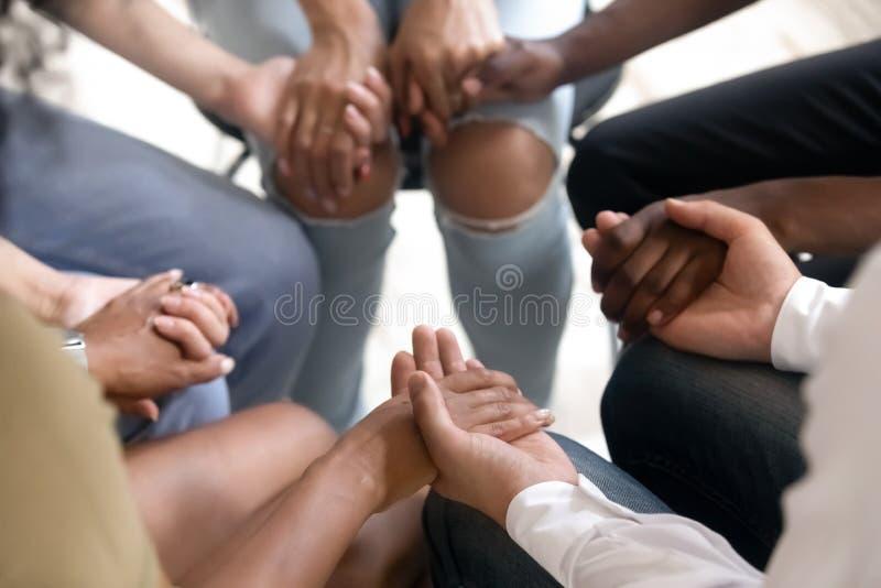 Olikt folk som sitter i cirkeln som rymmer händer på gruppterapi arkivbild