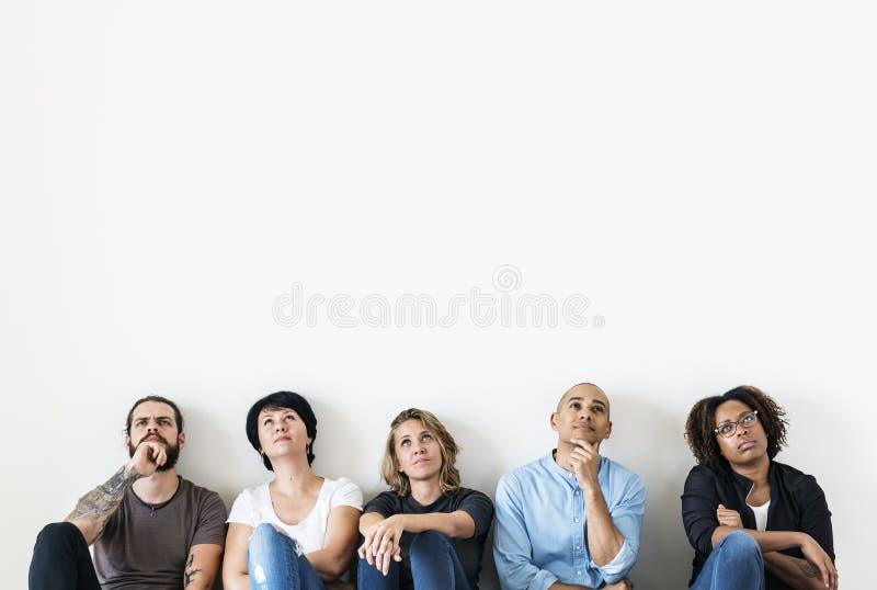 Olikt folk som sitter med fundersamt framsidauttryck royaltyfria foton