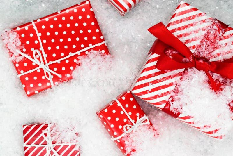 Olikt format som slås in i rött papper med askar för prydnadjulgåva på konstgjord snö royaltyfri bild
