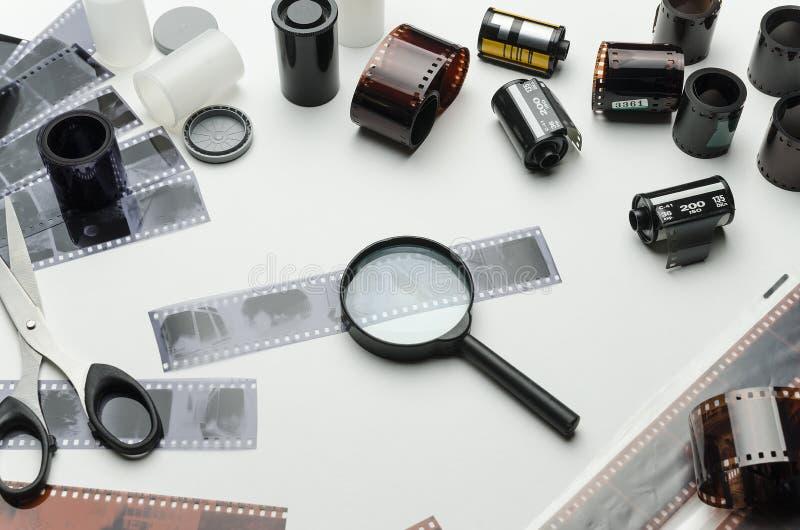 Olikt fotografiska filmer, sax och förstoringsglas på vit bakgrund royaltyfri bild