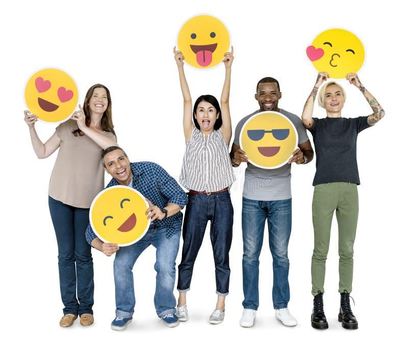 Olikt lyckligt folk som rymmer lyckliga emoticons royaltyfri bild