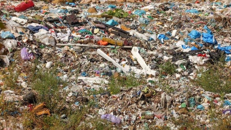 Olikt material kasserat på nedgrävning av sopor, gräs som omkring växer Inga logoer/varumärken som är synliga på dumpad avskräde royaltyfria foton