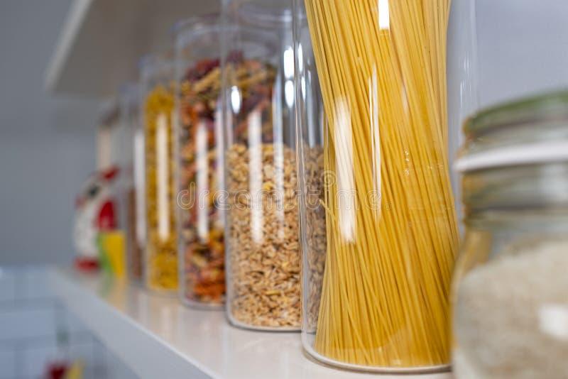 Olikt okokt livsmedel i exponeringsglaskrus som ordnas p? tr?hyllor arkivbilder