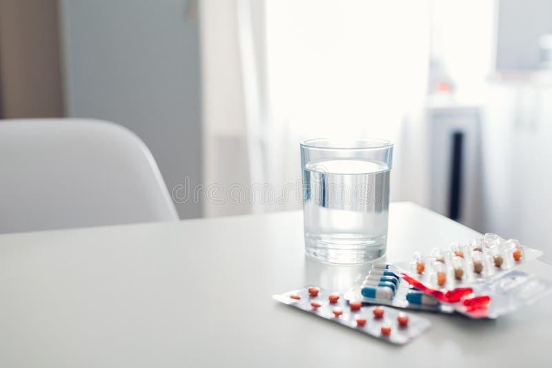Olikt piller och exponeringsglas av vatten p? k?ksbordet medicin f?r hygien f?r omsorgs?gonsjukv?rd royaltyfria foton