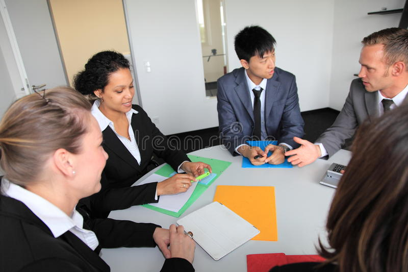 Olikt ungt affärslag i ett möte arkivfoto