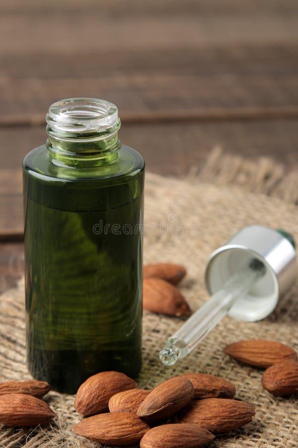 Olio cosmetico della mandorla naturale in una bottiglia di vetro ed in un primo piano fresco dei dadi della mandorla su una tavol immagini stock