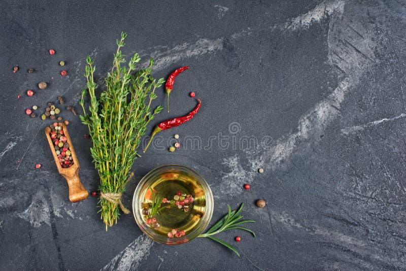 Olio d'oliva aromatico o condito in ciotola di vetro con le spezie e le erbe su fondo di marmo nero immagini stock libere da diritti