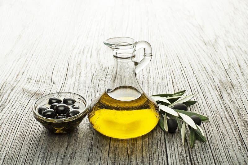 Olio d'oliva in bottiglia con le olive fotografia stock libera da diritti