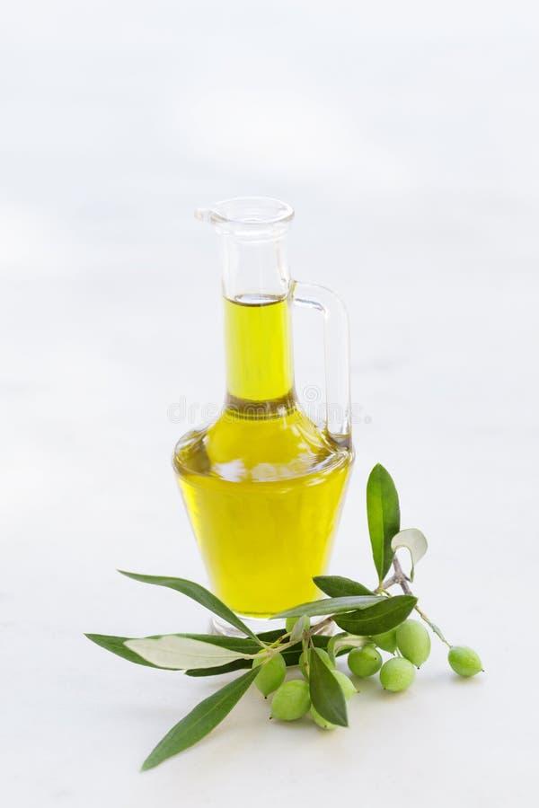 Olio d'oliva in bottiglia di vetro con le olive fresche sul ramo sulla tavola bianca fotografia stock libera da diritti