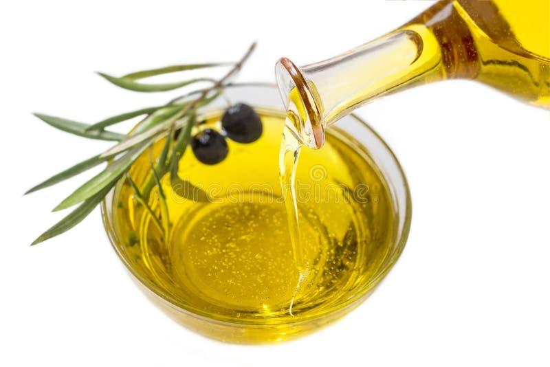 Olio d'oliva che versa in ciotola da una bottiglia e da una frutta matura su un fondo bianco fotografia stock