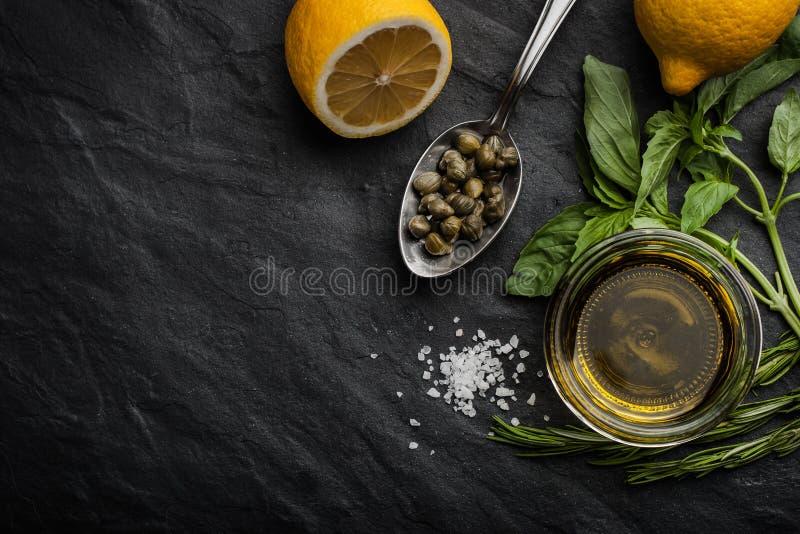 Olio d'oliva con il limone, i capperi ed i verdi differenti orizzontali fotografia stock