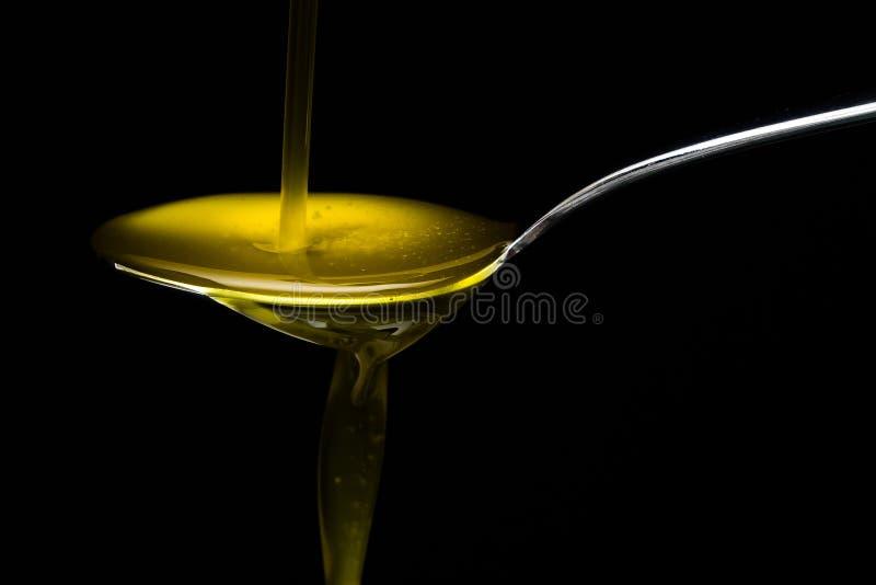 Olio d'oliva dorato sopra il cucchiaio del metallo fotografie stock libere da diritti