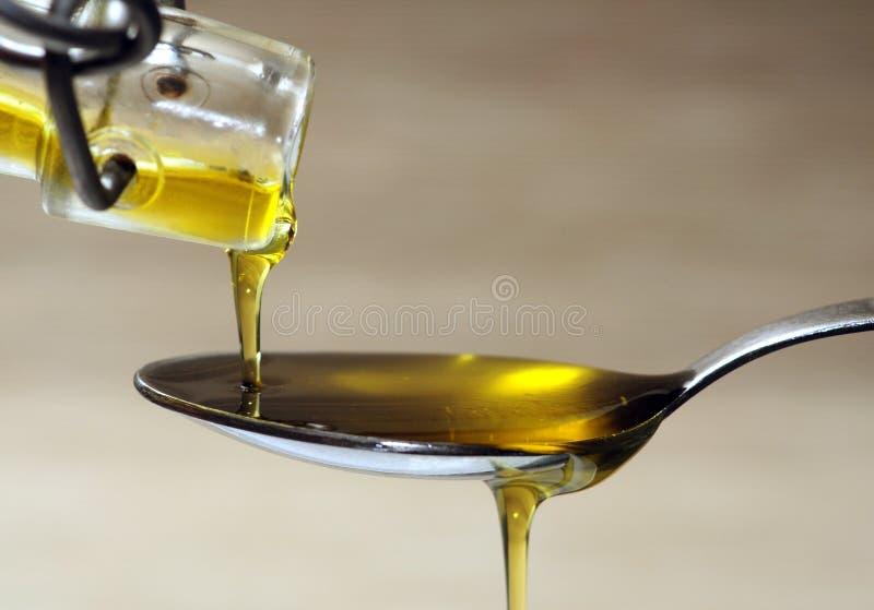 Olio d'oliva sopra il cucchiaio fotografia stock libera da diritti
