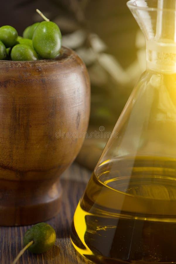 Olio d'oliva vergine extra in bottiglia di vetro con il ramo delle olive su fondo rustico Esaminando macchina fotografica fotografia stock