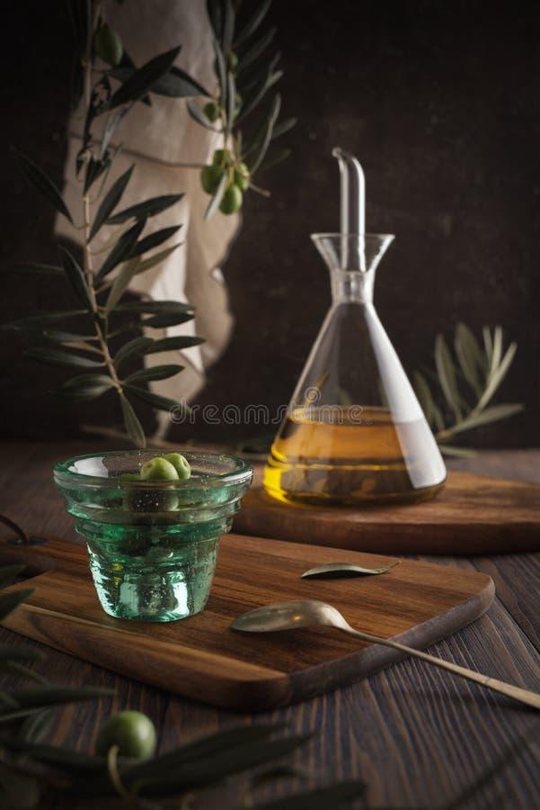 Olio d'oliva vergine extra in bottiglia di vetro con la tazza delle olive su fondo rustico Esaminando macchina fotografica fotografia stock