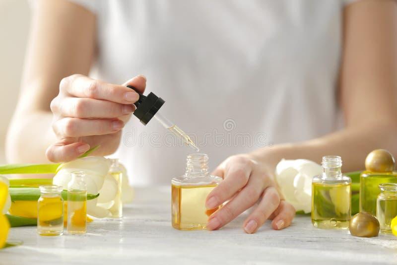 Olio della sgocciolatura della donna nella bottiglia di profumo immagine stock libera da diritti