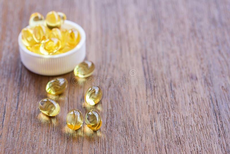 Olio di fegato di merluzzo Omega 3 capsule di gel su fondo di legno fotografia stock