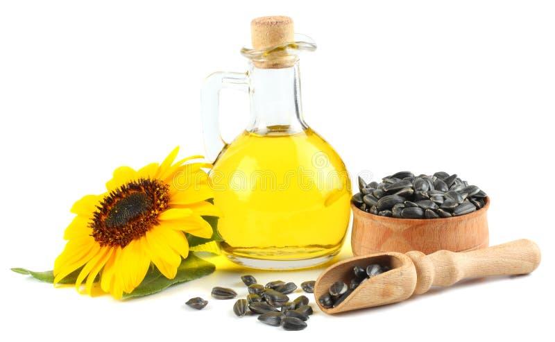 Olio di girasole in brocca, semi di vetro e fiore isolati su fondo bianco fotografie stock libere da diritti